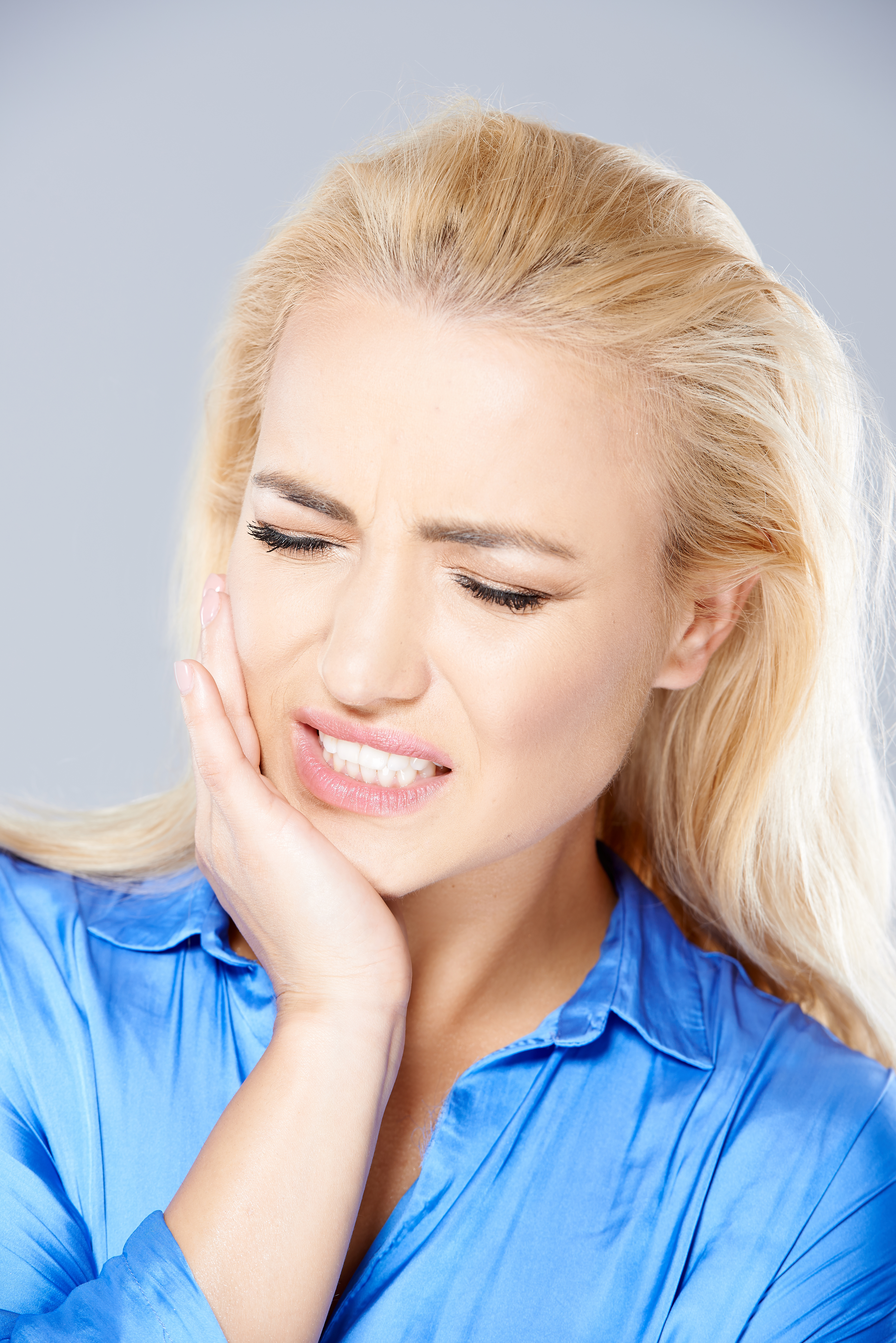 blond woman suffering from teeth grinding or bruxism